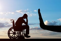 Concept of discrimination and disrespect for people with disabilities. Silhouette of sad disabled man in wheelchair and hand gesture stop. The concept of Stock Images