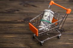 Concept dollar money banknotes in a shopping trolley. On wood texture background Royalty Free Stock Images