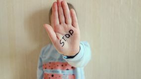 Concept of domestic violence and child abusement. A little girl shows her hand with the word STOP written on it. Children violence stock video footage