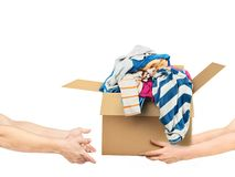 The concept of donating. Hands are giving a box of clothes to other hands. On a white background royalty free stock images
