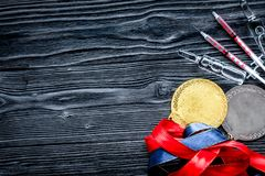 Concept of doping in sport - deprivation medals top view. On dark wooden background royalty free stock images
