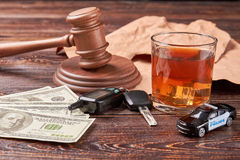 The concept of drink driving. Amount of money, car keys, gavel, whiskey, police car on wooden background. Money penalty for drunk drivers Royalty Free Stock Photography