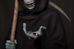 The concept: drugs kill. Grim reaper holding syringe with drugs Stock Image