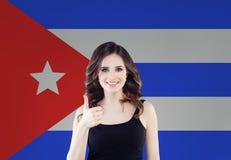 Concept du Cuba d'amour avec la femme heureuse souriant et montrant le pouce sur le fond de drapeau de Cubains images stock