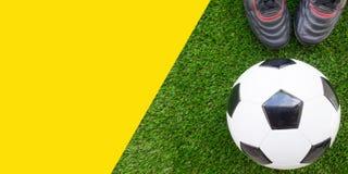 Concept du football : Ballon de football du football avec de vieilles bottes du football dessus Images stock