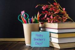 Concept du jour du professeur Objets sur un fond de tableau Livres, pomme verte, plaque : Le jour, les crayons et les stylos du p Image stock
