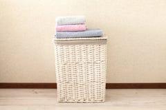 Concept du processus de blanchisserie Panier de blanchisserie en osier avec les serviettes color?es photos stock