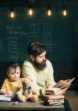 Concept du relevé Livre de lecture de professeur à l'écolier Le petit enfant écoutent le livre de lecture de l'homme dans la clas Images stock