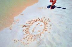 Concept du repos d'été par la mer Sur le bord de la mer dans le sable a peint un soleil de sourire Smiley sur le sable dans la li Photo libre de droits
