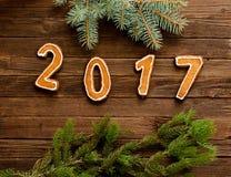 Concept du `s d'an neuf Le chiffre en 2017 du pain d'épice sur un fond en bois, branche de fourrure-arbre au bord du cadre Images stock