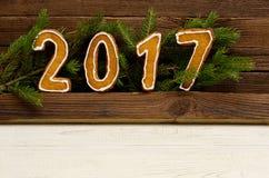 Concept du `s d'an neuf Le schéma 2017 du pain d'épice, branche de sapin sur un fond en bois Photo libre de droits