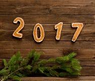 Concept du `s d'an neuf Le schéma 2017 du pain d'épice, branche de sapin sur un fond en bois Photos stock