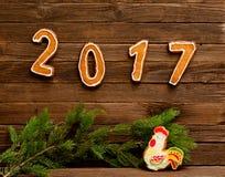 Concept du `s d'an neuf Le schéma 2017 et coq du pain d'épice, branche de sapin sur un fond en bois Images libres de droits