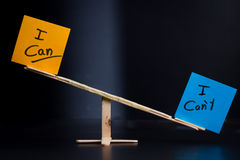 Concept for duality. Concept of duality using sticky notes with antonyms on a hand made sea saw on a dark background Royalty Free Stock Images