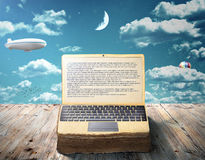 The concept of e-book. An open book as laptop. Lies on a wooden table against the sky. Writing Royalty Free Stock Image