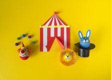 The concept of Easter with cute and cheerful handmade eggs. A rabbit, a clown, a strongman and a lion.Circus Yellow background. Funny egg. Painted Easter eggs Royalty Free Stock Photo