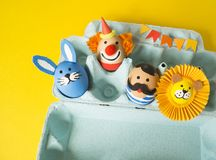 The concept of Easter with cute and cheerful handmade eggs. A rabbit, a clown, a strongman and a lion.Circus Yellow background. Funny egg. Painted Easter eggs Stock Photo