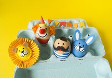 The concept of Easter with cute and cheerful handmade eggs. A rabbit, a clown, a strongman and a lion.Circus Yellow background. Funny egg. Painted Easter eggs Stock Photography
