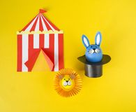 The concept of Easter with cute and cheerful handmade eggs. A rabbit, a clown, a strongman and a lion.Circus Yellow background. Funny egg. Painted Easter eggs Stock Photos