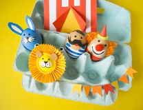 The concept of Easter with cute and cheerful handmade eggs. A rabbit, a clown, a strongman and a lion.Circus Yellow background. Funny egg. Painted Easter eggs Royalty Free Stock Photography
