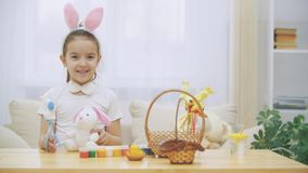 Little cute and adorable girl is smiling and playing with Easter bunnies in her hands. Concept Easter holiday.