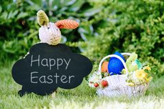Toy bunny with chalk text Happy Easter on blackboard and basket with eggs, flowers and berries. Royalty Free Stock Photo
