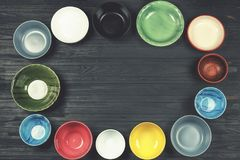 Food, cooking, Multicolored bowls, utensils, concept, black tabl. Concept of eating, cooking. Multicolored bowls on a black wooden table with copy space Stock Photography