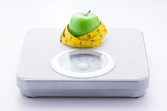 Concept of eating healthy and maintaining good body. Apple and tape measure on bathroom scale isolated on white background. Royalty Free Stock Image