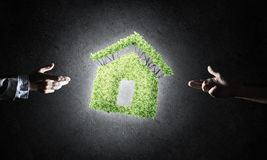 Concept of eco architecture presented by green house on dark bac. Close of businessman hand and green house icon as symbol of save construction Stock Photo