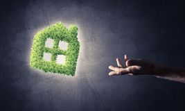 Concept of eco architecture presented by green house on dark bac. Close of businessman hand and green house icon as symbol of save construction Stock Photos