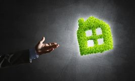 Concept of eco architecture presented by green house on dark background Royalty Free Stock Image
