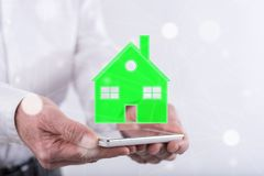 Concept of eco friendly house. Eco friendly house concept above a smartphone held by hands Royalty Free Stock Image