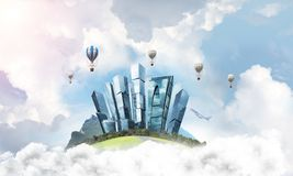 Concept of eco friendly life. Green flying island among clouds with urban view of towers and skyscrapers. Flying aerostates and blue cloudy skyscape on Royalty Free Stock Photos