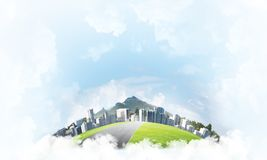 Concept of eco green life as elegant business center on white clouds. Modern cityscape with buildings and skyscrapers floating on clouds in sky Stock Images
