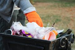 Volunteer cleans garbage in the park and throws it in the trash can royalty free stock photo