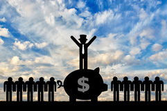 Concept of economic inequality. Rich man standing on a big piggy Bank with money next to ordinary people Stock Photography