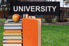 A concept of education. With book, apple, and university word stock photography