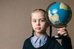 Concept - education. Caucasian girl holding a globe. Charming little girl holding a globe, looking at camera stock images