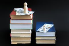 Concept of education and income. Wooden figures dollars and books on a black background.  stock photos