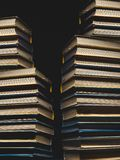 Concept Of Education And Knowledge. Tower Building Of Old Multicolored Books On A Black Background royalty free stock image