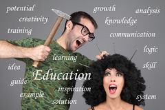 Concept - Education, Learning, Tutor. Putting information in head. A man is hammering nails into a girl's head. Stock Images