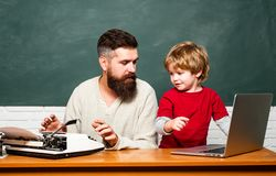 Concept of education and teaching. Teacher helping pupils studying on desks in classroom. Copy space. Elementary school. Young or adult. Dad son are stock photo