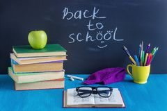 Workplace pupil Books Stationery Glasses and green Apple on blu stock image