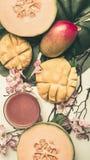 Concept een vegetarisch, gezond voedsel, een verse gesneden mango en een meloen met smoothies, met bloemen en bladeren van monste stock afbeelding