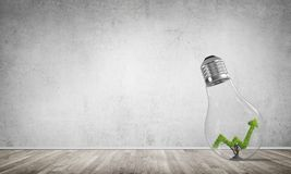 Concept of effective marketing innovations. Glass lightbulb with growing green arrow graph inside in empty room with grey wall on background. 3D rendering Stock Image