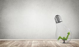 Concept of effective marketing innovations. Glass lightbulb with growing green arrow graph inside in empty room with grey wall on background. 3D rendering Stock Photo