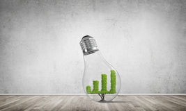 Concept of effective marketing innovations. Glass lightbulb with growing green graph inside in empty room with grey wall on background. 3D rendering Royalty Free Stock Image