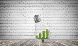Concept of effective marketing innovations. Glass lightbulb with growing green graph inside in empty room with grey wall on background. 3D rendering Stock Photo
