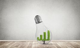Concept of effective marketing innovations. Glass lightbulb with growing green graph inside in empty room with grey wall on background. 3D rendering Stock Photography