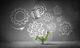Concept of effective marketing innovations. Lightbulb with growing green arrow graph inside placed against sketched gear mechanism on grey wall on background Stock Photo